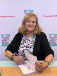 Pam Newton signing a book about a parent