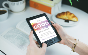 A pair of hands with a gold bracelet holds an electronic copy of The Good Around Us by Sylvia Pullen. In the background there is an open book, two coffee mugs, and a croissant on a plate.